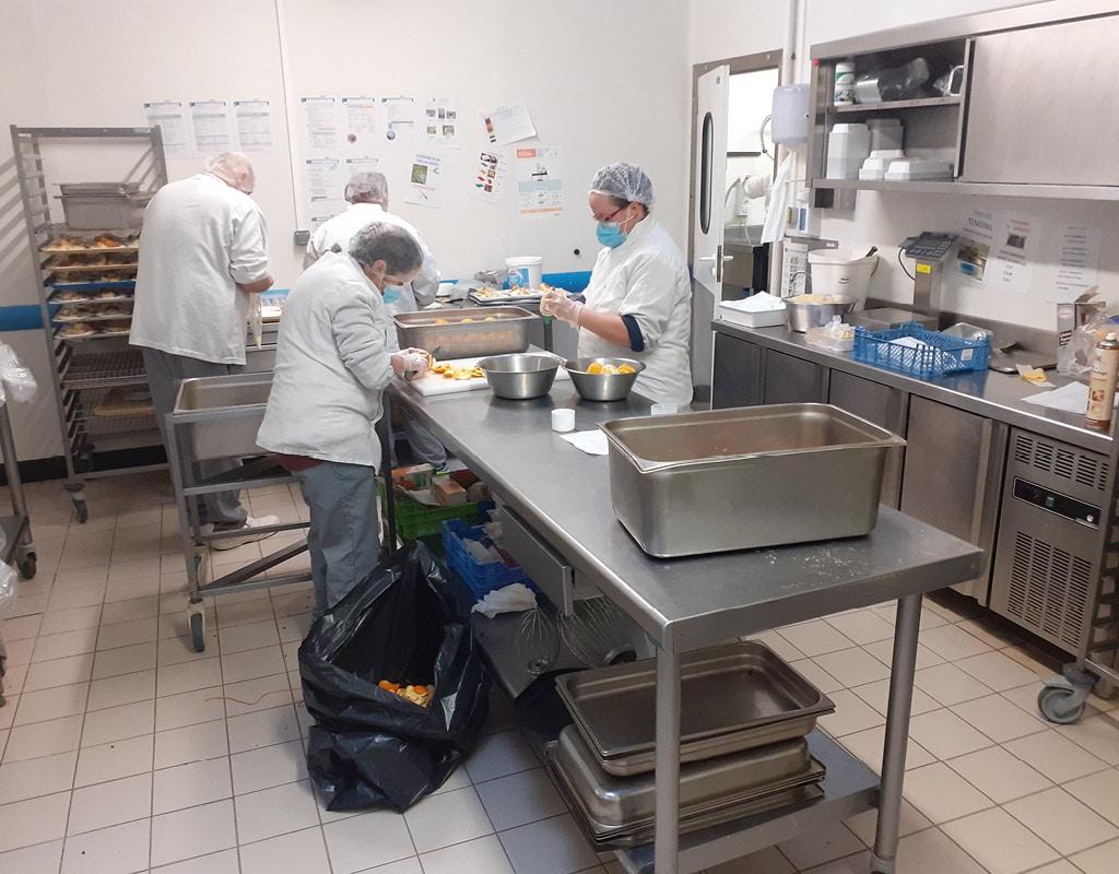 personnel d'ESAT en train de peler des oranges dans une cuisine centrale d'ESAT