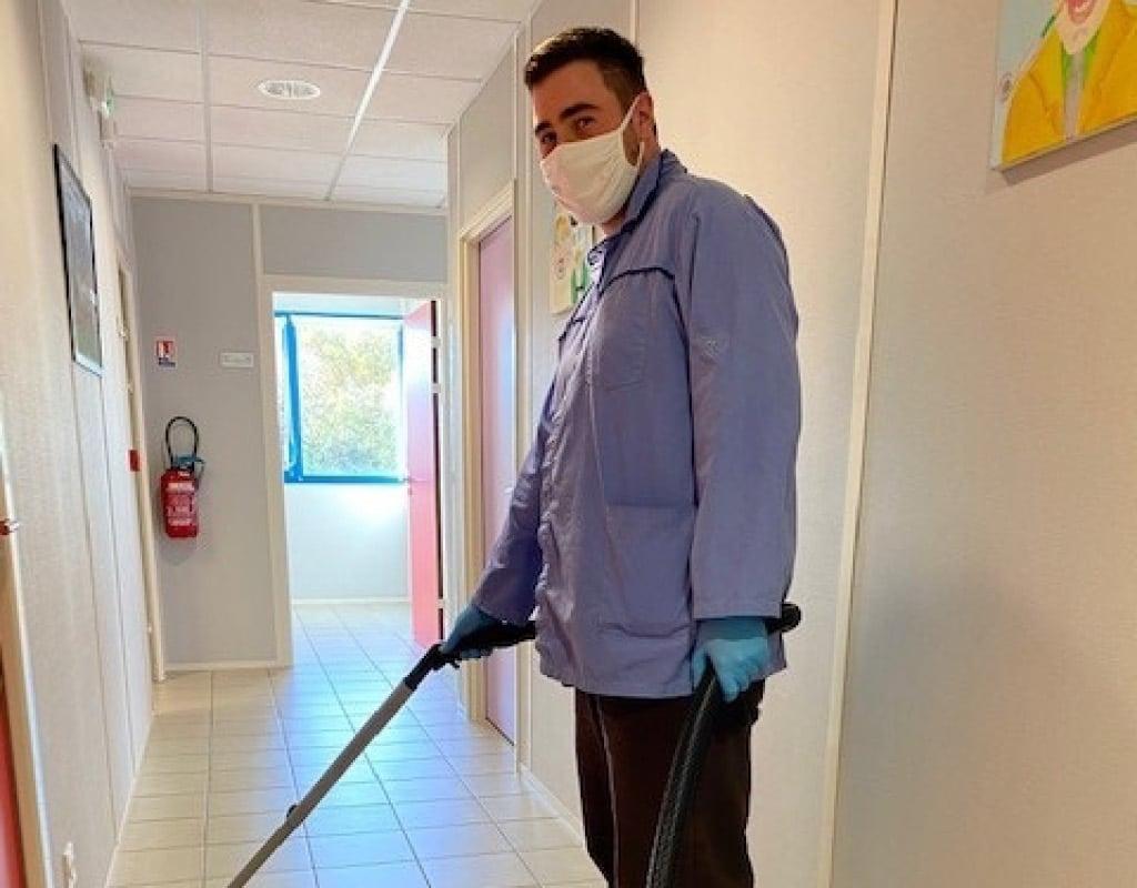 Employé en situation de handicap passant l'aspirateur dans un couloir
